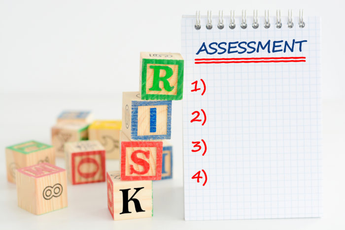 Risk assessment or management plan with wooden letter cubes and notebook