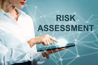 Risk Assessment text with business woman using a tablet