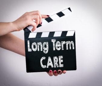 long term care concept. Female hands holding movie clapper.
