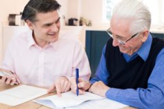 Man Helping Senior Neighbor With Financial Affairs