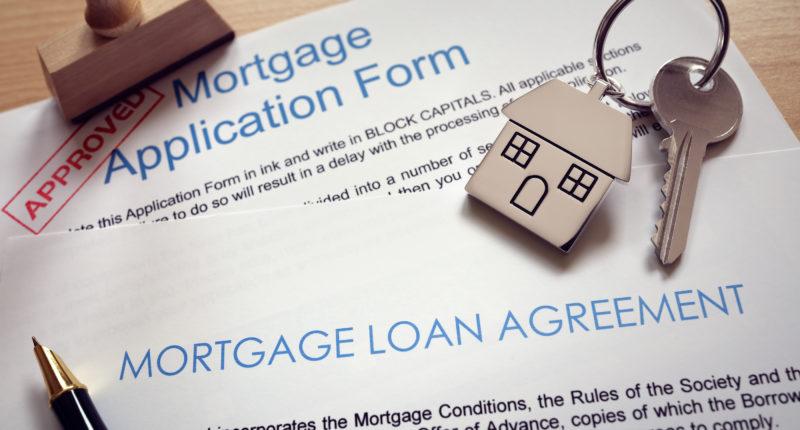 Mortgage loan agreement application with  key on house shaped ke