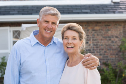 Portrait of a happy senior couple smiling in front of their hous