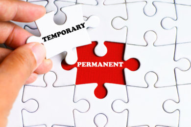 """""""PERMANENT"""" word on missing puzzle with a hand hold a piece of """"TEMPORARY"""" word puzzle want to complete it - business and finance concept"""