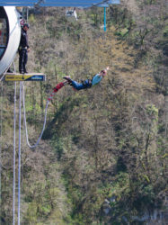Sochi - April 4 2017: A man in blue clothes with a rubber rope jumping from the world's longest pedestrian bridge in the Akhshtyr gorge April 4 2017 Sochi Russia