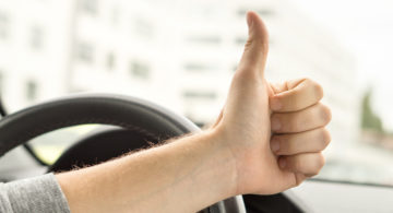 Happy driver showing thumbs up in car. Satisfied with new car or no traffic. Passed driving school test or vehicle inspection. Vehicle fixed and repaired.